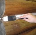 Шпателем герметик разравнивается вдоль шва деревянного дома